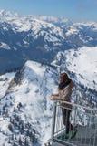 Bella ragazza castana sul terrazzo di un chalet nelle alte montagne Una ragazza e un giorno di estate nelle montagne Fotografia Stock
