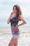 Bella ragazza castana in un breve vestito nel mare Fotografia Stock