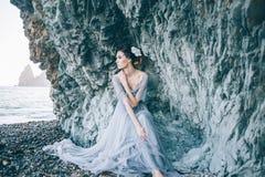 Bella ragazza castana in un vestito grigio lungo con un velo che si siede dal mare, fotografia stock