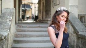 Bella ragazza, castana, in vestito lungo blu scuro con pizzo, corona, posante stock footage