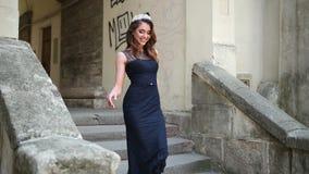 Bella ragazza, castana, in vestito lungo blu scuro con pizzo, corona, posante archivi video