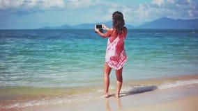 Bella ragazza castana in vestito rosso ed occhiali da sole che prendono selfie ed immagine sulla spiaggia sabbiosa 1920x1080 archivi video