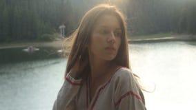 Bella ragazza castana in vestito unico dal ricamo e con il sole in suoi capelli scuri lunghi in un lago soleggiato della montagna stock footage