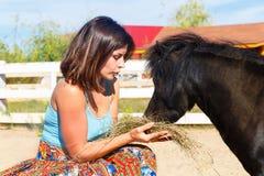 Bella ragazza che alimenta il cavallino della paglia sull'azienda agricola fotografie stock