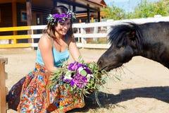 Bella ragazza che alimenta il cavallino della paglia sull'azienda agricola fotografie stock libere da diritti