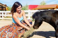 Bella ragazza che alimenta il cavallino della paglia sull'azienda agricola immagini stock libere da diritti