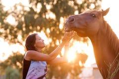 Bella ragazza che alimenta il suo cavallo bello Immagini Stock