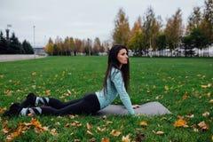 Bella ragazza che allunga all'erba Giovane atleta femminile castana sportivo sulla stuoia di yoga - cane ascendente del rivestime Fotografia Stock Libera da Diritti