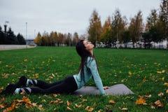 Bella ragazza che allunga all'erba Giovane atleta femminile castana sportivo sulla stuoia di yoga - cane ascendente del rivestime Immagine Stock