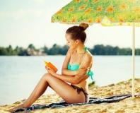 Bella ragazza che applica la crema di abbronzatura sulla sua pelle Fotografie Stock Libere da Diritti