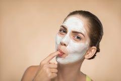 Bella ragazza che applica maschera crema facciale e fotografia stock