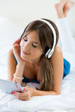 Bella ragazza che ascolta la musica con la compressa sul sofà a casa Immagine Stock