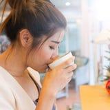 Bella ragazza che beve caffè o tè caldo in caffè del caffè immagini stock