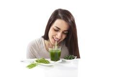 Bella ragazza che beve succo verde fotografia stock
