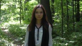 Bella ragazza che cammina nella foresta verde frondosa video d archivio