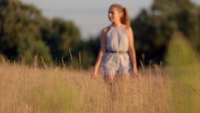 Bella ragazza che cammina sul campo con erba alta nei raggi del tramonto archivi video