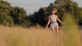 Bella ragazza che cammina sul campo con erba alta nei raggi del tramonto stock footage