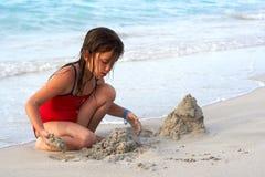 Bella ragazza che costruisce un castello della sabbia nella spiaggia Immagini Stock