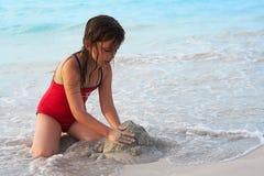 Bella ragazza che costruisce un castello della sabbia nella spiaggia Immagini Stock Libere da Diritti