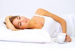 Bella ragazza che dorme con una tazza di caffè Fotografia Stock
