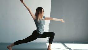 Bella ragazza che fa esercizio di yoga allungamenti femminili prima di una classe di yoga Allungamento armi e delle gambe stock footage