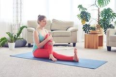 Bella ragazza che fa posa di yoga sulla stuoia di yoga dell'interno Immagine Stock Libera da Diritti