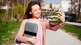 Bella ragazza che fa selfie dallo smartphone con il computer portatile vicino al parco Fotografie Stock