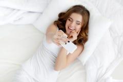 Bella ragazza che fa selfie nel letto Immagini Stock