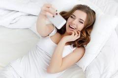Bella ragazza che fa selfie nel letto Fotografie Stock