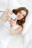 Bella ragazza che fa selfie nel letto Fotografia Stock