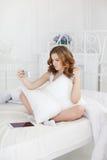 Bella ragazza che fa selfie nel letto Immagine Stock