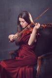 Bella ragazza che gioca lle fiddle con gli occhi chiusi fotografia stock