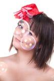 Bella ragazza che guarda attraverso le bolle fotografia stock