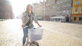 Bella ragazza che guida una bicicletta nella vecchia città, luce solare all'aperto video d archivio