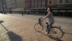 Bella ragazza che guida una bicicletta nella vecchia città, luce solare all'aperto stock footage