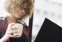 Bella ragazza che lavora al suo computer portatile mentre bevendo caffè fotografia stock