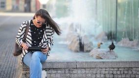 Bella ragazza che legge e che passa in rassegna un libro elettronico o una compressa che si siede in un banco alla via, fondo del archivi video