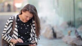 Bella ragazza che legge e che passa in rassegna un libro elettronico o una compressa che si siede in un banco alla via, fondo del stock footage