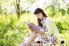 Bella ragazza che legge un libro che si siede sull'erba Fotografia Stock