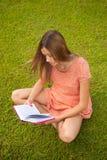 Bella ragazza che legge un libro che si siede sull'erba Fotografia Stock Libera da Diritti