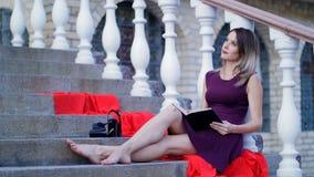 Bella ragazza che legge un libro che si siede sulle scale archivi video
