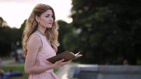 Bella ragazza che legge un libro in un parco e che sogna dell'amore archivi video