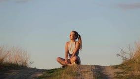 Bella ragazza che medita su collina nei raggi del tramonto stock footage