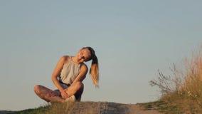 Bella ragazza che medita su collina nei raggi del tramonto archivi video