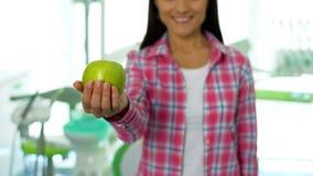 Bella ragazza che mostra mela verde alla macchina fotografica nell'ufficio dentario, denti sani fotografia stock
