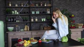 Bella ragazza che parla sul telefono cellulare in cucina a casa archivi video