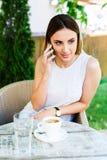 Bella ragazza che parla sul telefono mentre caffè dei dinks e che si siede al caffè Fotografia Stock Libera da Diritti