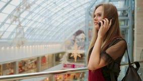 Bella ragazza che parla sullo smartphone e che si siede con i sacchetti della spesa in centro commerciale stock footage