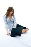Bella ragazza che per mezzo del computer portatile Fotografia Stock