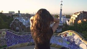 Bella ragazza che pettina capelli con la mano sul parco di Barcellona Goda del viaggio della Spagna stock footage